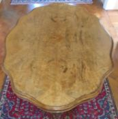 A Superb scalloped edge Walnut Centre Table with highly decorated base on brass castors.