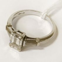 18 CT. GOLD EMERALD CUT RING CENTRE STONE (1.18 CARAT) WITH DIAMONDS TO THE SHOULDER - SIZE J
