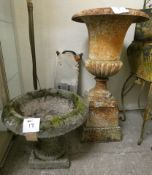 A cast iron urn shape planter, raised on a square base, 88 cm, together with a reconstituted stone