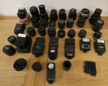 A collection of camera lens and flashes, to include Sigma, Nikon and Canon.