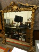 A Victorian/Edwardian wood and plaster gilt over mantle mirror with floral spay supports, 177 x