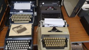 Four typewriters with cases; Silver Reed, two Adler and an Olympia (4).