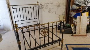 A Victorian cast iron and brass double bed, with castors, one strap missing, 140 cm.