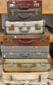 A green canvas covered suitcase and 6 other suitcases (7).