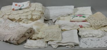 A hand crocheted single bed spread, a quantity of table cloths, bedsheets and line.
