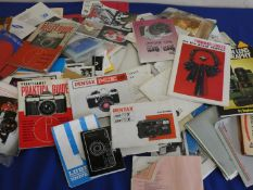 A collection of camera accessories, to include flash, a large quantity of camera manuals and slide