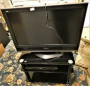 A Panasonic Viera 32 inch LCD TV on smoked glass 3 tier stand and a Panasonic DVD player.