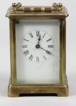 A brass carriage time piece, the white enamel dial unsigned, height with handle raised 14 cm.