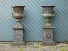 A Victorian good quality pair of cast iron garden urns, twin handle with gadrooned borders and