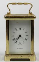 A French brass carriage time piece, the white enamel dial signed H. Samuel, the 7 jewel movement