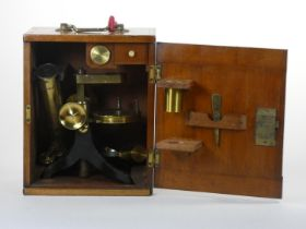 Fred. J. Cox, Eastbourne, a Victorian brass and cast iron microscope, with three different lens,
