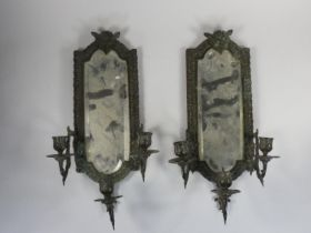 A pair of bronzed metal wall sconces, with bevelled glass mirrors, the three scones with mask bases,