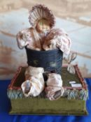 An early 20th Century antique style musical automaton, in the form of a macabre baby doll in basket;