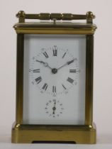 A brass carriage striking, repeating and alarm clock, the white enamel dial unsigned, subsidiary