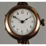 A 9ct rose gold ladies manual wind wristwatch, London 1910, the white enamel dial with red 12,