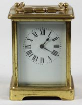 A French brass carriage time piece, the white enamel dial unsigned, the movement stamped Made in