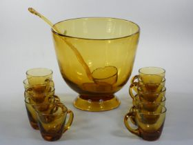 A hand blown amber glass punch bowl, ladle and ten cups, c. 1960/70, unsigned, diameter 25 cm