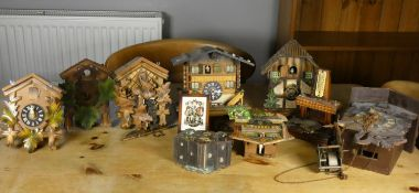 A collection of eight various Cuckoo clocks, in need of repair, together with a Bavarian ashtray
