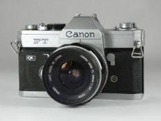 WITHDRAWN A Canon FT-QL 35mm SLR camera, together with a Canon 28mm f3.5 lens and a leather case