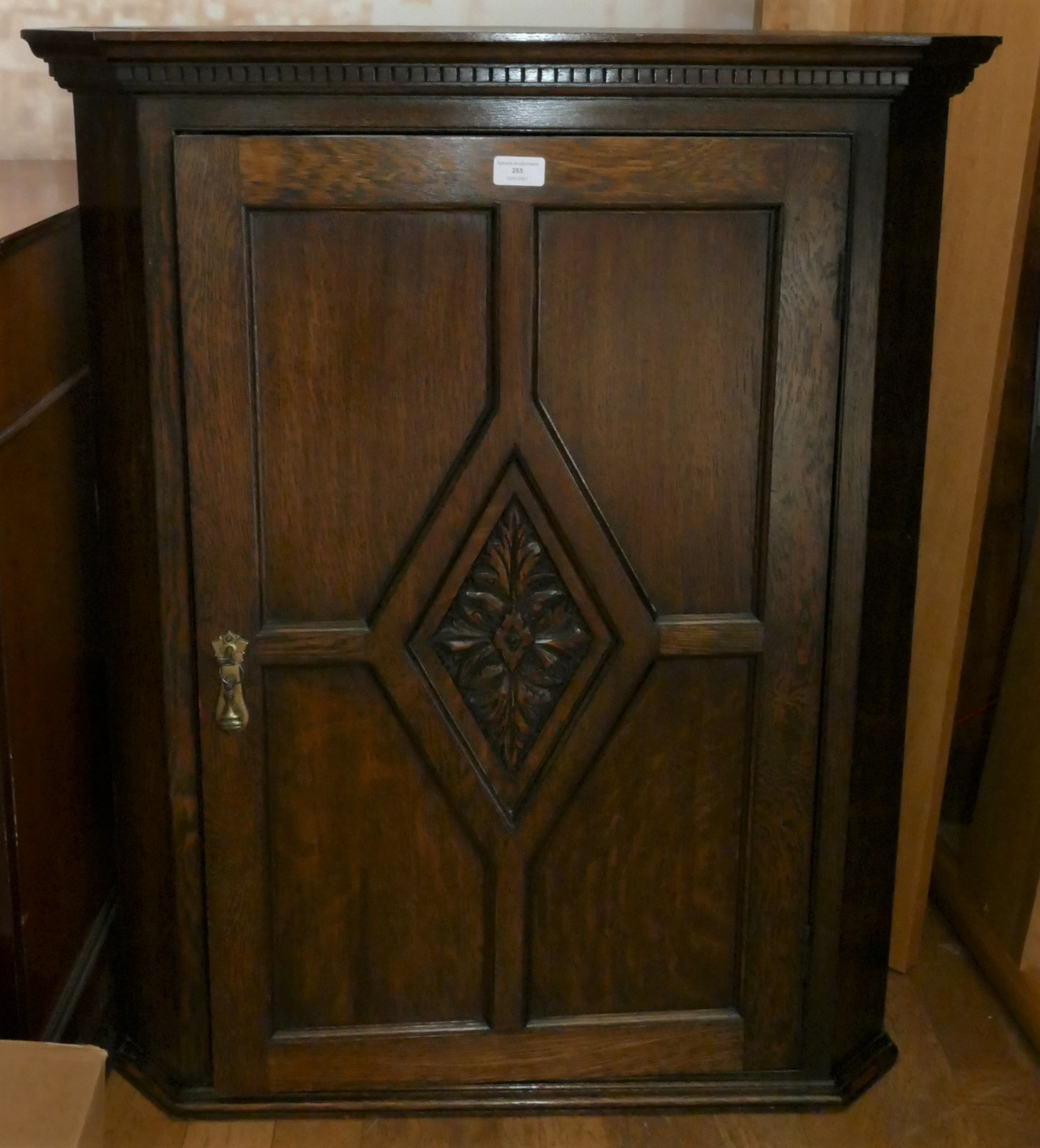 A late 19th early 20th Century carved oak corner cabinet. The four panel fielded feature door, opens