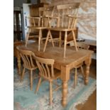 A stripped pine dining table with drawer to one end, together with a set of six pine chairs. (two