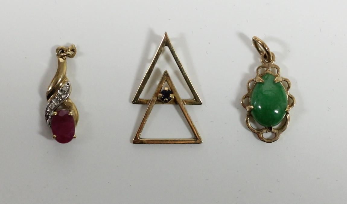 A ruby and diamond pendant, a jade pendant and another pendant