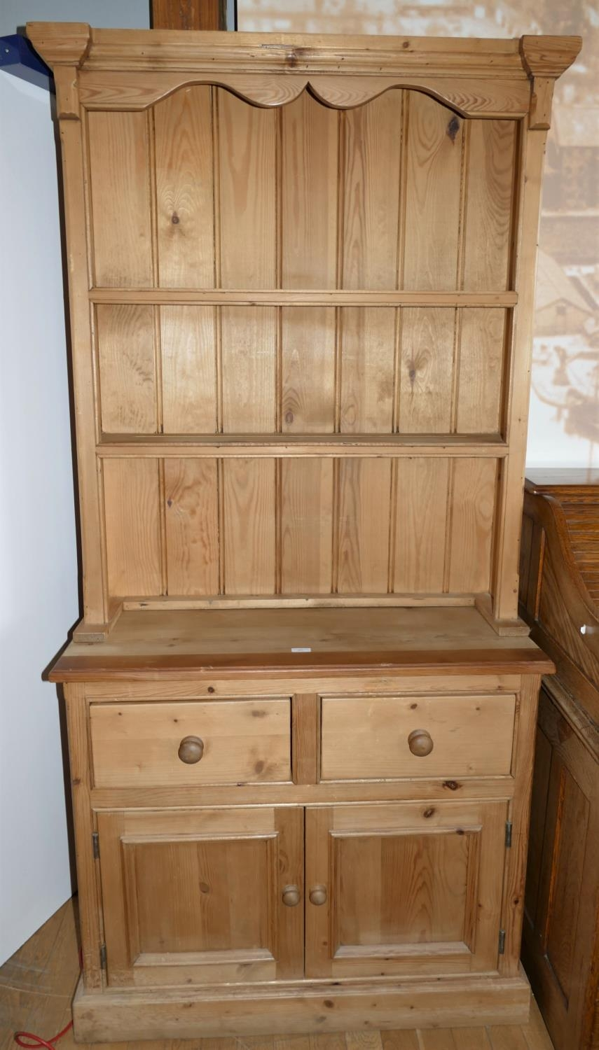 A traditional pine dresser, the base having two drawers between two cupboards with turned wooden