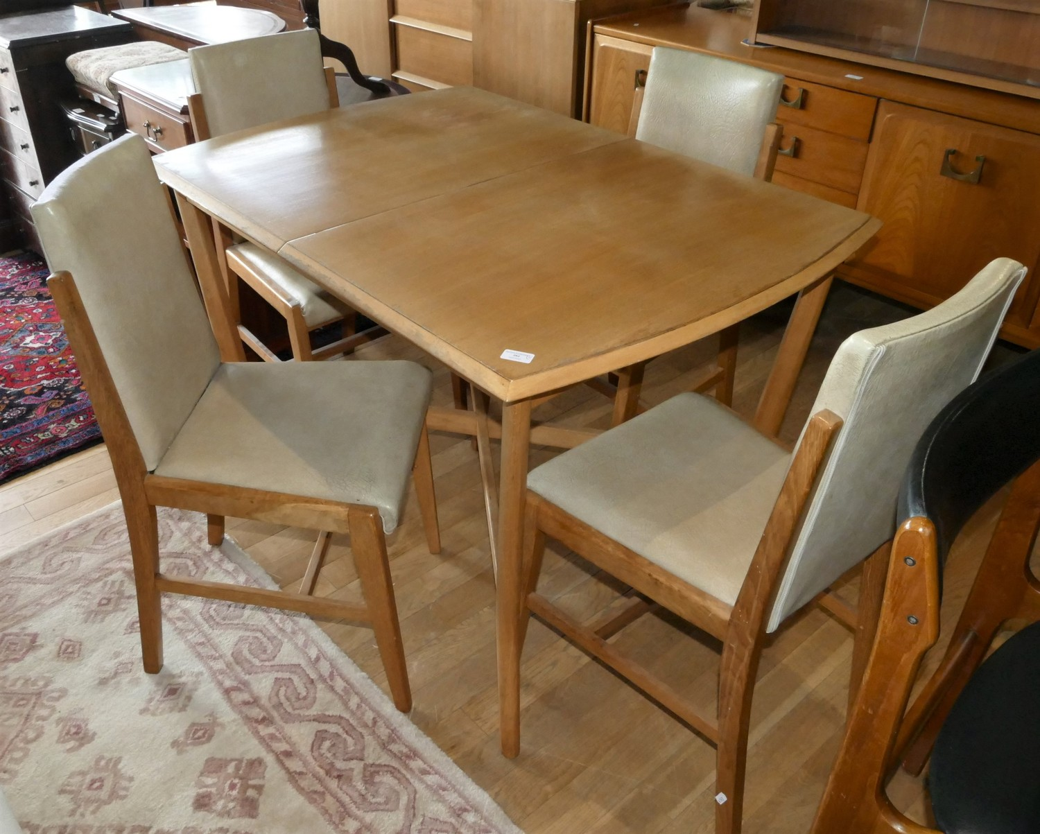 A Mid Century Deco style teak dining suite comprising of a extending dining table with integral leaf