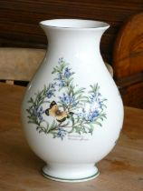 A Royal Worcester flower vase of bulbous for, decorated with herbs. 26cm tall.