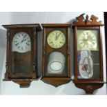 A collection of clocks to include, a William Dale quartz wall clock, together with other wooden wall