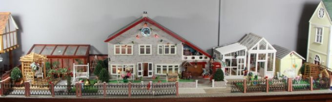A large hand built dolls house diorama, composed of a two story chalet type house with integral