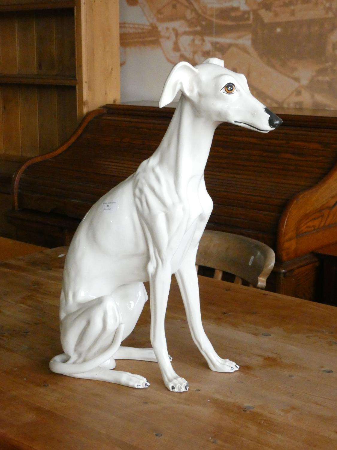 A ceramic fireside model of a seated Whippet dog. 54cm tall.