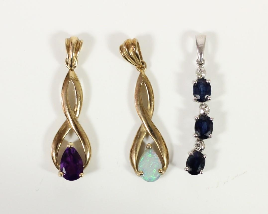 A 9ct gold opal drop pendant, a similar amethyst example and a sapphire pendant, 2.5gm.