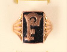A 9ct rose gold and onyx signet ring, letter F, reeded shoulders,