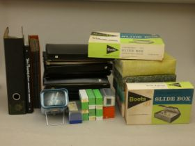 A collection of 35mm slide holders, 35mm film storage folders, slide wheels and empty photo