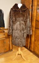 A ladies mid length brown and a full length silver fur coats