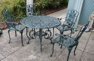 A cast metal garden dining set, painted dark green with floral decoration, with four