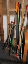 A collection of hand and garden tools, including a hose on reel, a bio-green phoenix heater along