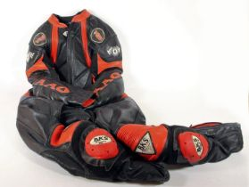 A BKS black and red leather made to measure one piece suit, 52cm across the shoulders, matching