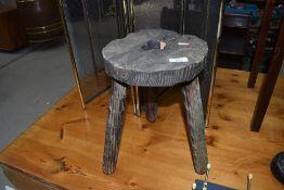 A rustic legged milking stool