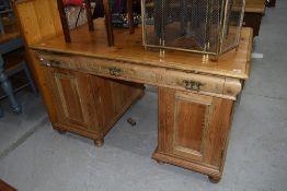 A large rustic pine twin pedestal desk, having ornate brass handles, width approx. 140cm depth 88cm