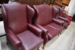 A modern three piece wing back lounge suite , in wine red leather