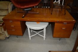 A vintage office desk, in teak, highly polished, with Chromed handles and legs, and very similar