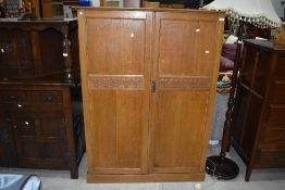 An Arts and Crafts style golden oak compactum style wardrobe, having carved heart motifs to doors,
