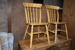 A pair of traditional rubberwood kitchen chairs
