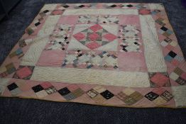 A large Victorian patchwork quilt, using various wool and wool blend fabrics, around a double in