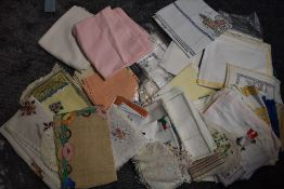 A large lot of vintage table linen,some having embroidery,also included are beaded milk jug covers.