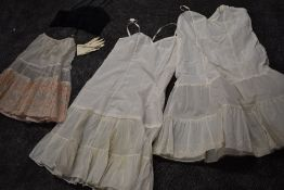 A collection of vintage petticoats one having beautiful flocked floral pattern and a long line black
