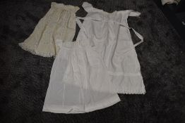 Three antique items of baby clothing including one long gown with cut work and embroidered hem,