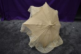 An early 20th century cream slub silk parasol with an abundance of tulle lace surrounding the